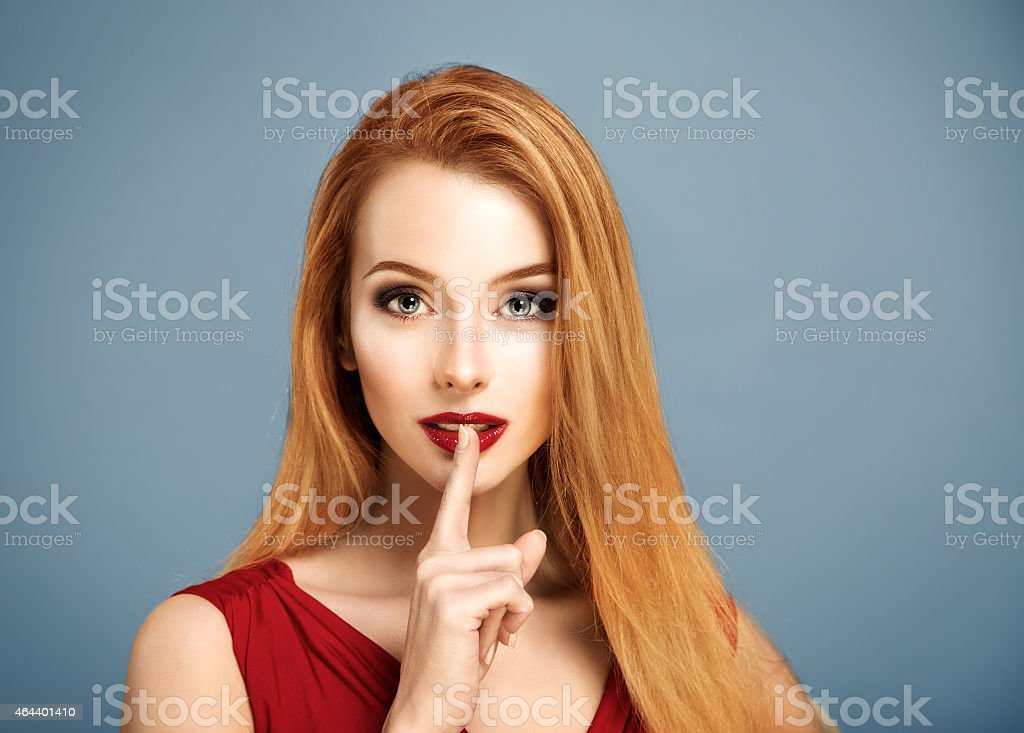 Hush. Sexy Woman with Finger on her Lips. stock photo