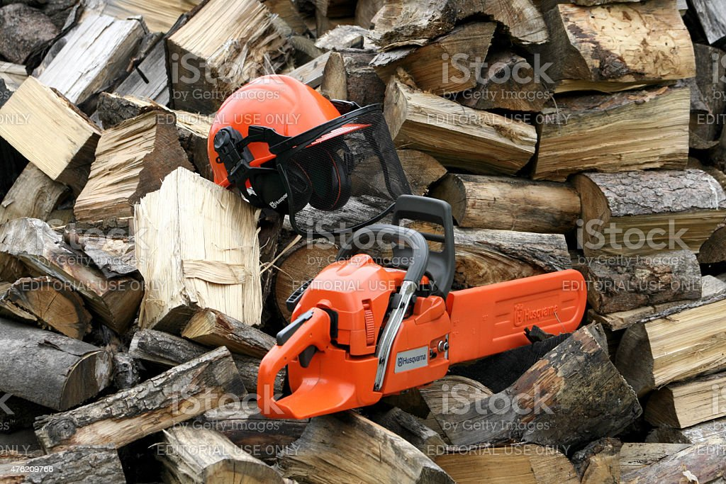 Husqvarna chainsaw and helmet on wooden pile stock photo