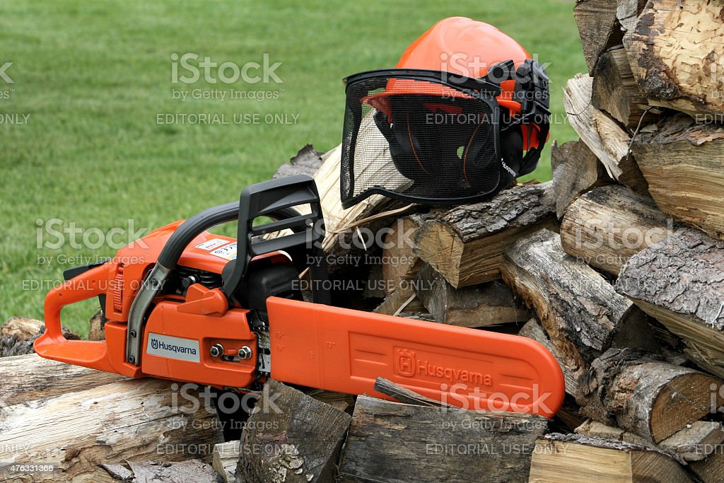 Husqvarna chainsaw with protective helmet and firewood stock photo