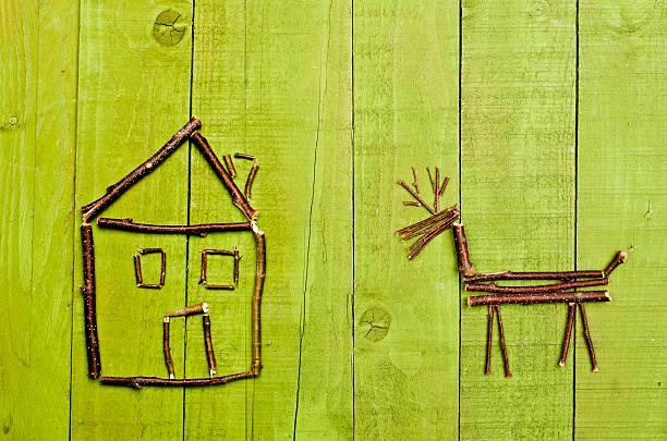 Hut and reindeer aranged from sticks on wooden green backgraund. - foto de acervo