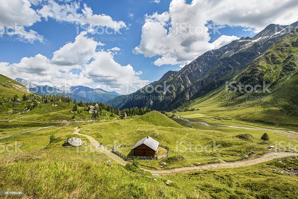 Hut in austrian alps with white clouds and blue sky stock photo