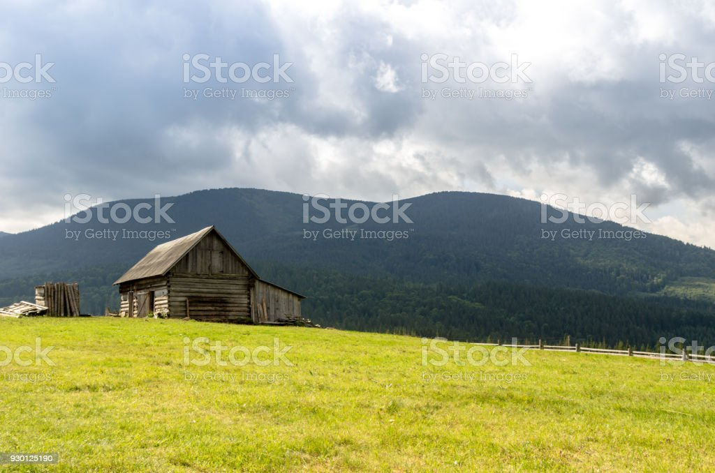 A hut in the mountains. Wooden house in the mountains. The house is made of log house. stock photo