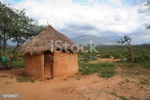 A mud hut in Kenya, Africa.  The background has a beautiful mountain in it, with immersive, interesting lighting due to the oncoming storm.  The door of the hut has a cheap padlock on it, making for a potentially interesting metaphor.