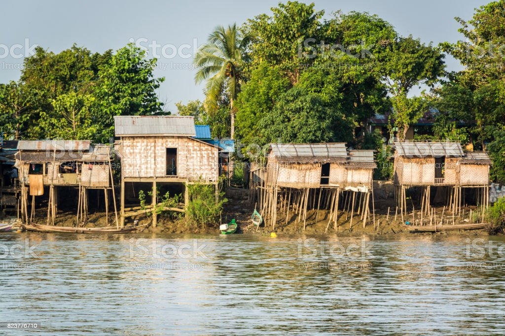 Huts on the riverbank at Burmese fishing village stock photo