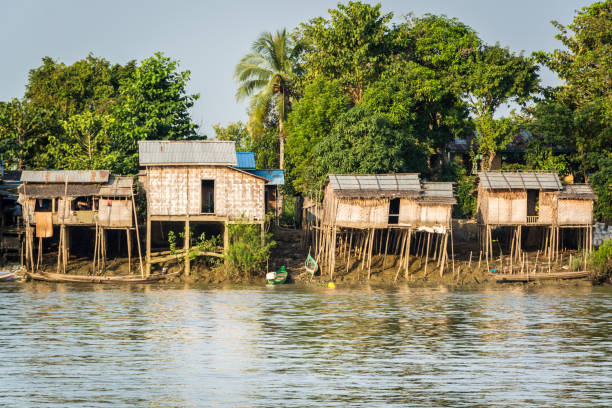 huts on the riverbank at burmese fishing village - burma home do стоковые фото и изображения