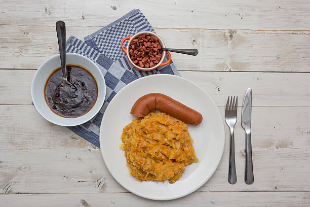 hutspot with smoked sausage on a white plate - stamppot stockfoto's en -beelden