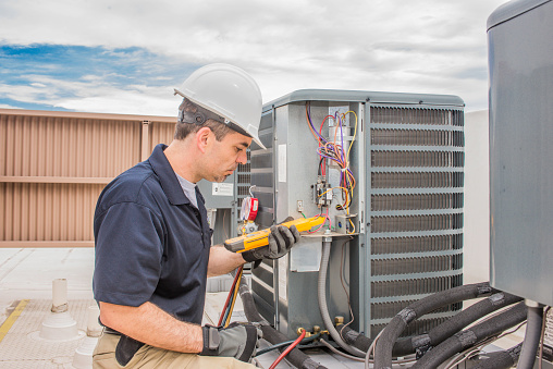 Trained hvac technician holding a voltage meter, performing preventative maintenance on a air conditioning condenser unit.