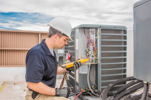 Hvac Tech working on a condensing unit Trained hvac technician holding a voltage meter, performing preventative maintenance on a air conditioning condenser unit. technician stock pictures, royalty-free photos & images