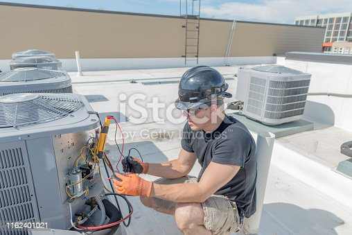 Hvac tech holding a volt meter, working on a condensing unit on a roof top.