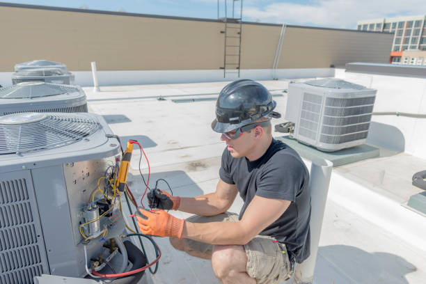 HVac Technician working on condenser panel Hvac tech holding a volt meter, working on a condensing unit on a roof top. air duct stock pictures, royalty-free photos & images