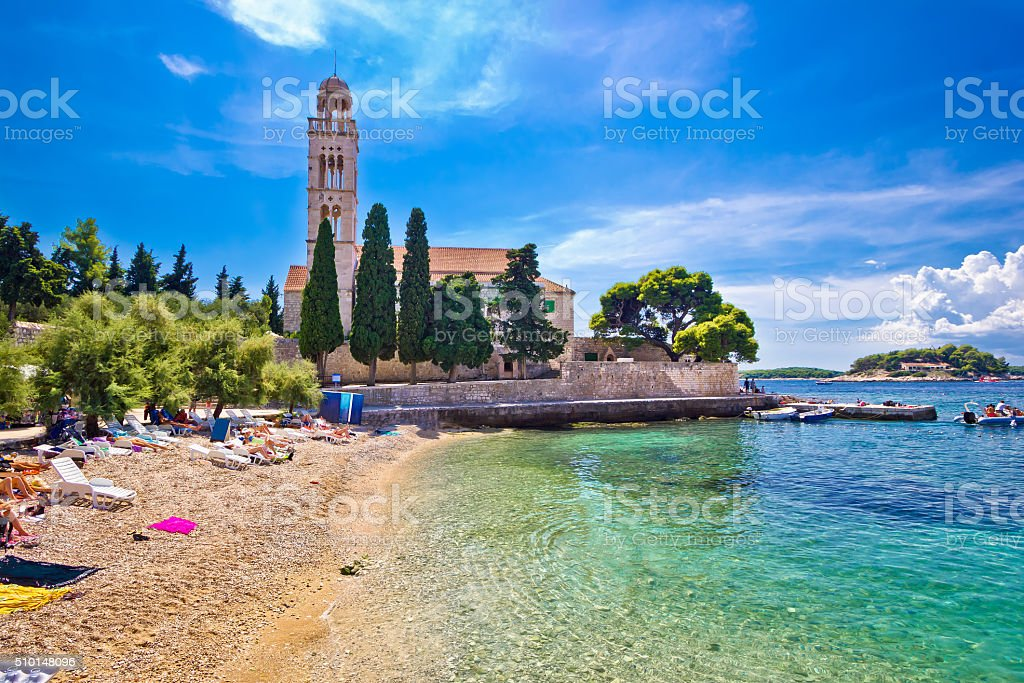 Hvar island turquoise beach and stone church stock photo