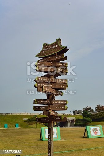 A finger post sign indicating the distances and directions of many world cities from the Hwaseong Fortress in Suwon, South Korea.  The structures on the ground are shielding lighting equipment used to night time viewing.  The fortress wall is in the background. And the