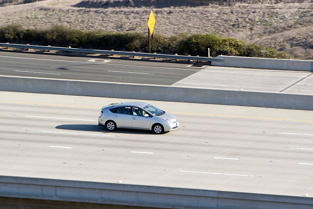 Hybrid Car (silver) A hybrid car heads down the highway. hybrid car stock pictures, royalty-free photos & images