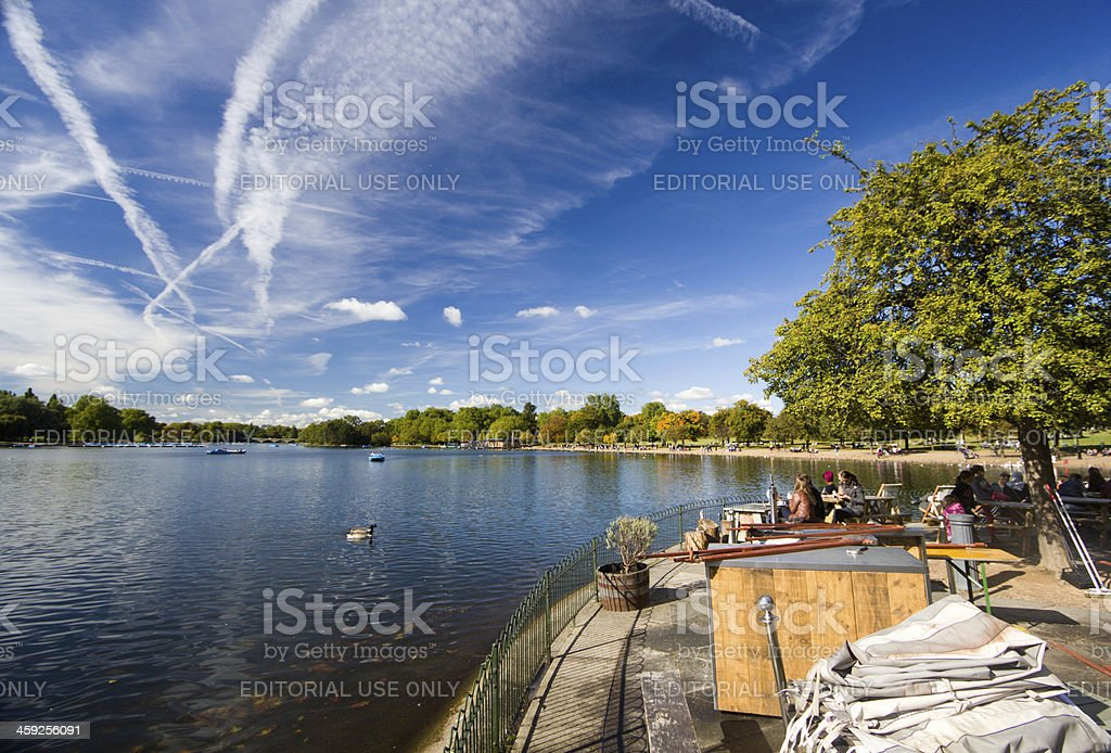 "Hyde Park in London, England ""London, England - October 6, 2012: An outdoor restaurant is patronised by people who are drinking beverages and eating refreshments on the shores of the Serpentine lake in Hyde Park, on an autumn afternoon in London."" Adult Stock Photo"