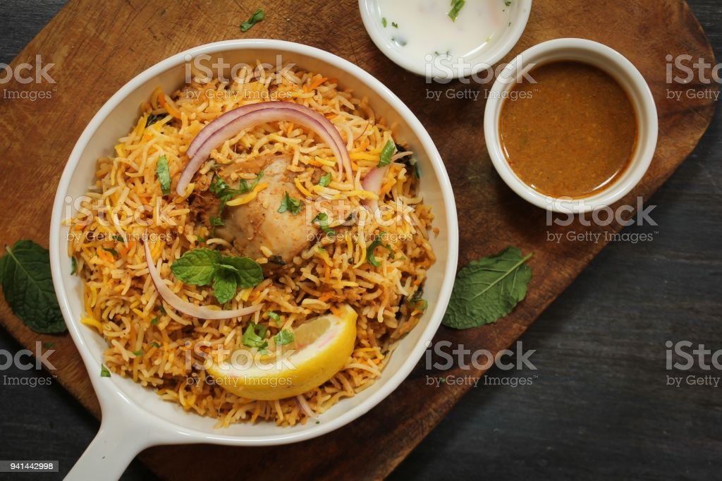 Hyderabadi Chicken Biryani served with Yogurt raita and Salan stock photo