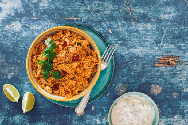 hyderabadi chicken biryani with cucumber raita on rustic table - chicken rice stock photos and pictures