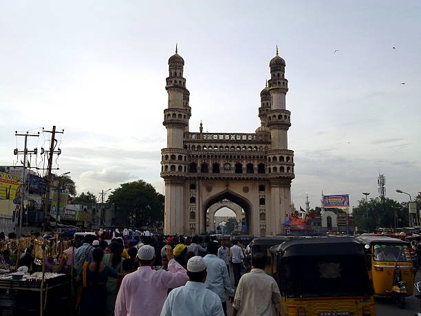 Hyderabad's Charminar view from the road Hyderabad, India - January 2, 2016: Hyderabad, India autorikshow waiting for passengers by the landmark Charminar tower. char minar stock pictures, royalty-free photos & images