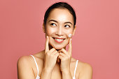 istock Hydrating and moisturizing. Young Asian woman applying face cream smiling and touching her cheeks against pink background 1211442654