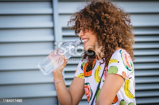 a young woman drinking water from a bottle on the street