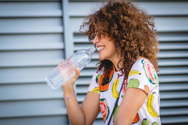 hydratatie tijdens de zomer. een jonge vrouw drinkt water - woman water stockfoto's en -beelden