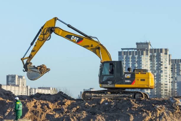 gato de escavadeira hidráulica rastreador trabalhando em um terreno. rússia. são petersburgo. 16 de janeiro de 2018. - lagarta - fotografias e filmes do acervo