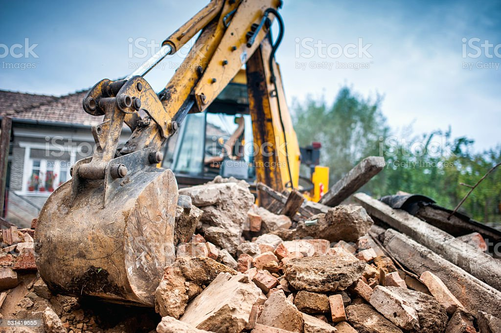 Hydraulic crusher excavator backoe machinery working on site demolition stock photo