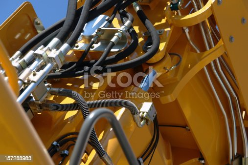 This is a technical closeup from the hydraulic system of a new, big excavator. There are many black hoses visible in the photo, and the yellow coated metal reflects the sun. The geometry visible in the photo's composition is quite complex.