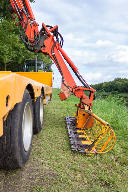 Hydraulic grab with cutter bar in verge of channel stock photo
