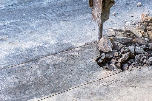 istock Hydraulic jackhammer crashing reinforced concrete road. 1135766039