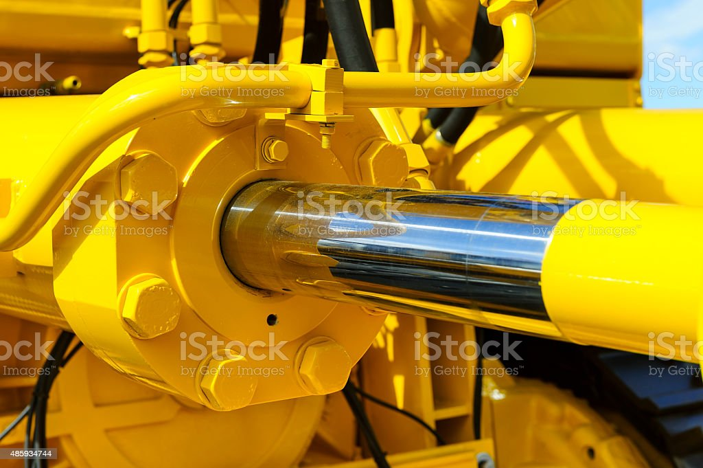 Hydraulic piston system Hydraulic piston system for bulldozers, tractors, excavators, chrome plated cylinder shaft of yellow machine, construction heavy industry detail, selective focus  2015 Stock Photo
