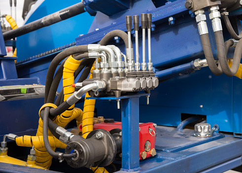 Hydraulic tubes, fittings and levers on control panel, close up of pipe system of hydraulic valves in agricultural machinery or lifting mechanism