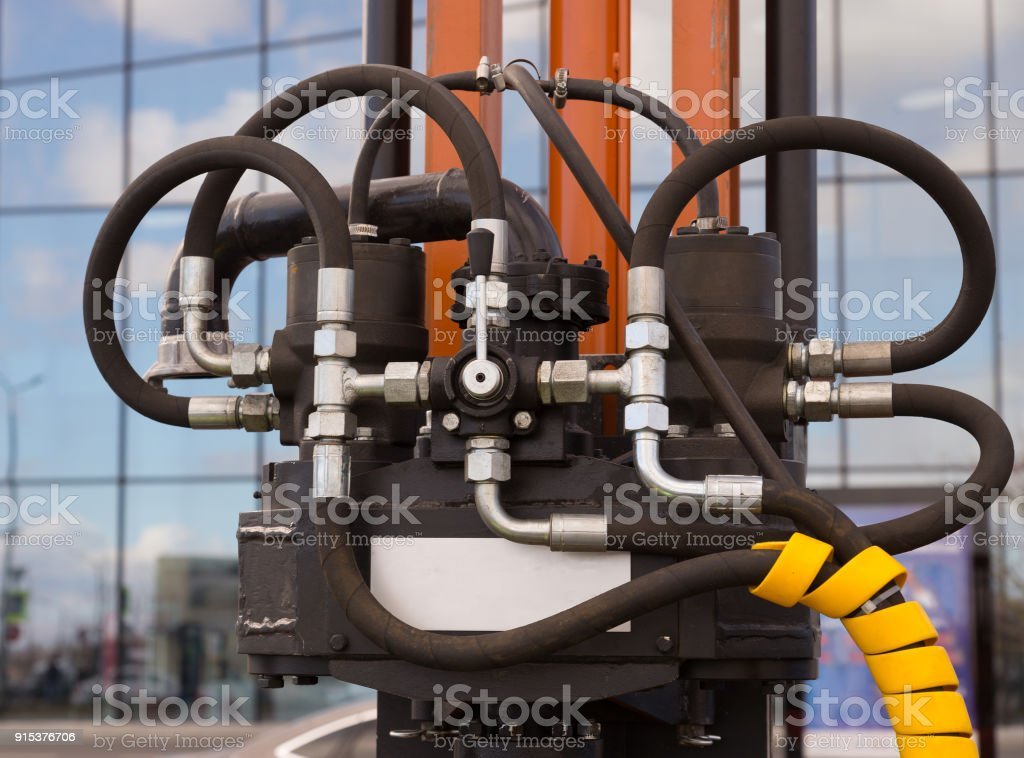 Hydraulic tubes fittings and levers on control panel of lifting mechanism stock photo