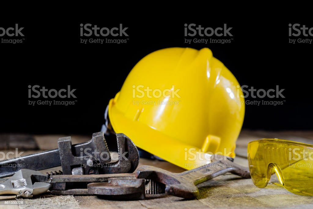 Hydraulics, tools for plumber on wooden table. Workshop, table and tools - adjustable spanner, connectors, keys. Black background stock photo
