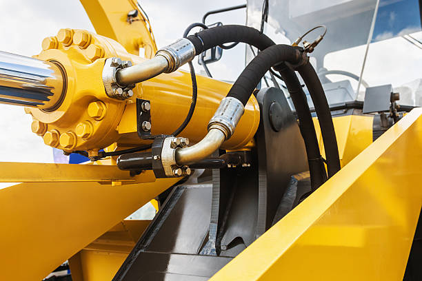 hydraulics tractor yellow hydraulics tractor yellow. focus on the hydraulic pipes construction machinery stock pictures, royalty-free photos & images