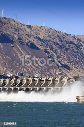 John Day hydroelectric facility on the Columbia River with wind turbines on nearby ridge.