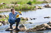 Man testing quality of natural water