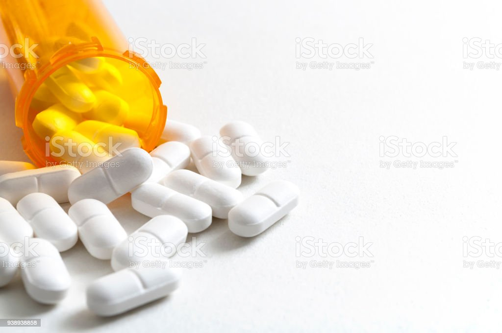 Hydrocodone capsules spilling out of a prescription bottle with copyspace stock photo