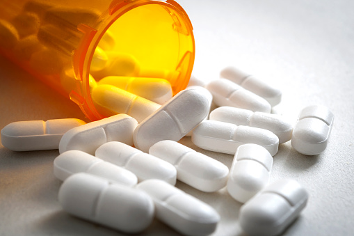 Opioid epidemic, painkillers and drug abuse concept with close up on a bottle of prescription drugs and hydrocodone pills falling out of it on white