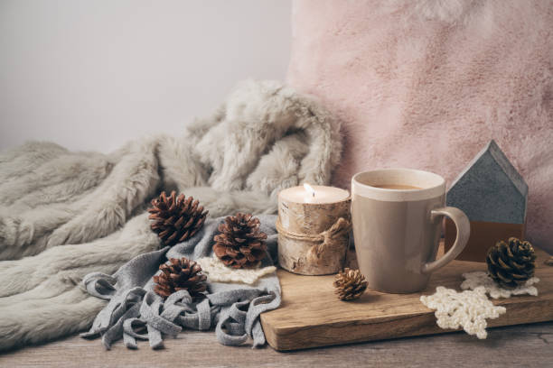 hygge scandinavian style concept with coffee cup, candles and pine corn - hygge imagens e fotografias de stock