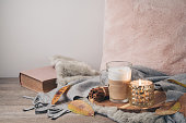 Hygge Scandinavian style concept with latte macchiato coffee cup, candles and book