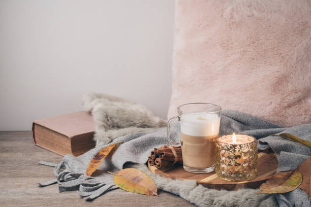 hygge skandinavischen stil konzept mit latte macchiato kaffee tasse, kerzen und buch - herbst kerzen stock-fotos und bilder