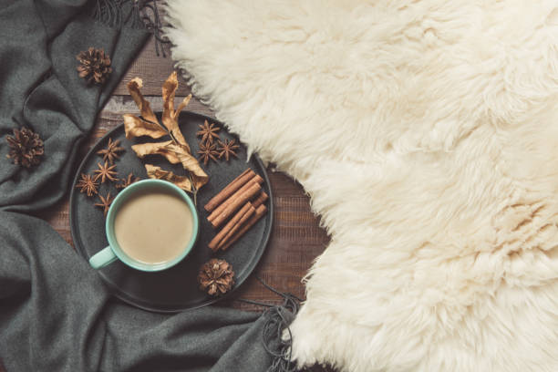 hygge still life with hot cup of black coffee, anise, warm scarf on furskin and wooden board. copy space. top view. - hygge imagens e fotografias de stock