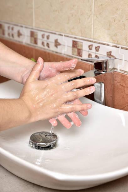 Higiene. Limpieza de manos. Lavarse las manos con jabón. Joven se lava las manos con jabón sobre el lavabo en el baño, primer plano. Covid 19. Coronavirus. - foto de stock