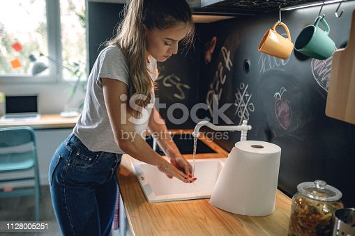 Woman washing hands in kitchen