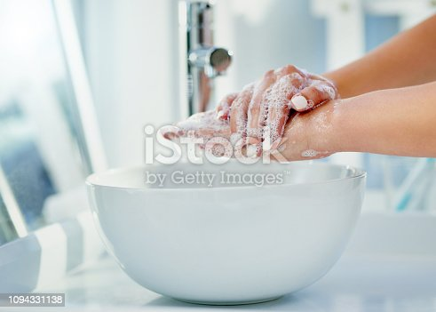 Cropped shot of a woman washing her hands with soap in the bathroom basin at home