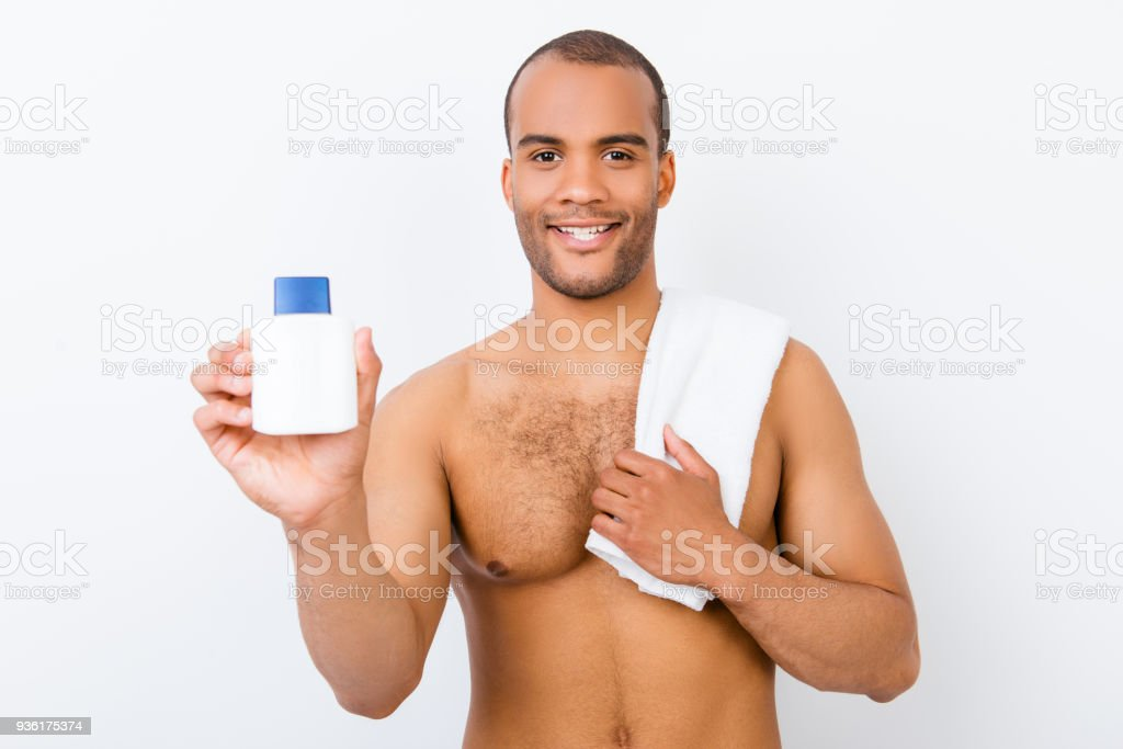 Hygiene, vitality, beauty, men life concept. Young smiling nude afro guy with towel and product in his arm is making advertisement stock photo
