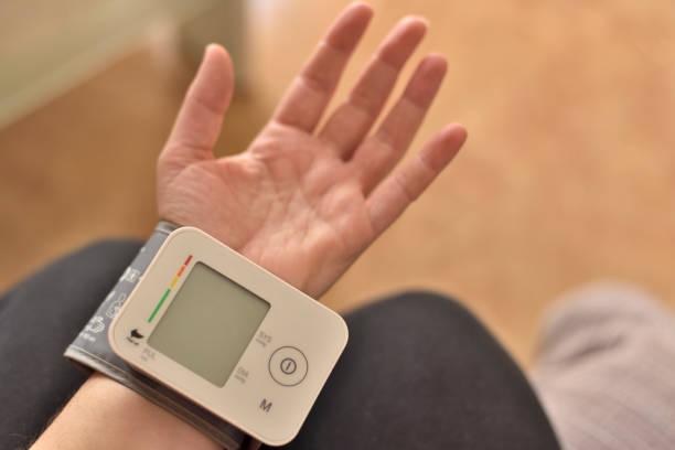 Paciente hipertenso que realiza una presión arterial automática - foto de stock