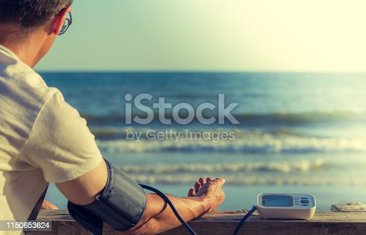 istock Hypertensive patient performing an automatic blood pressure test on the beach 1150653624