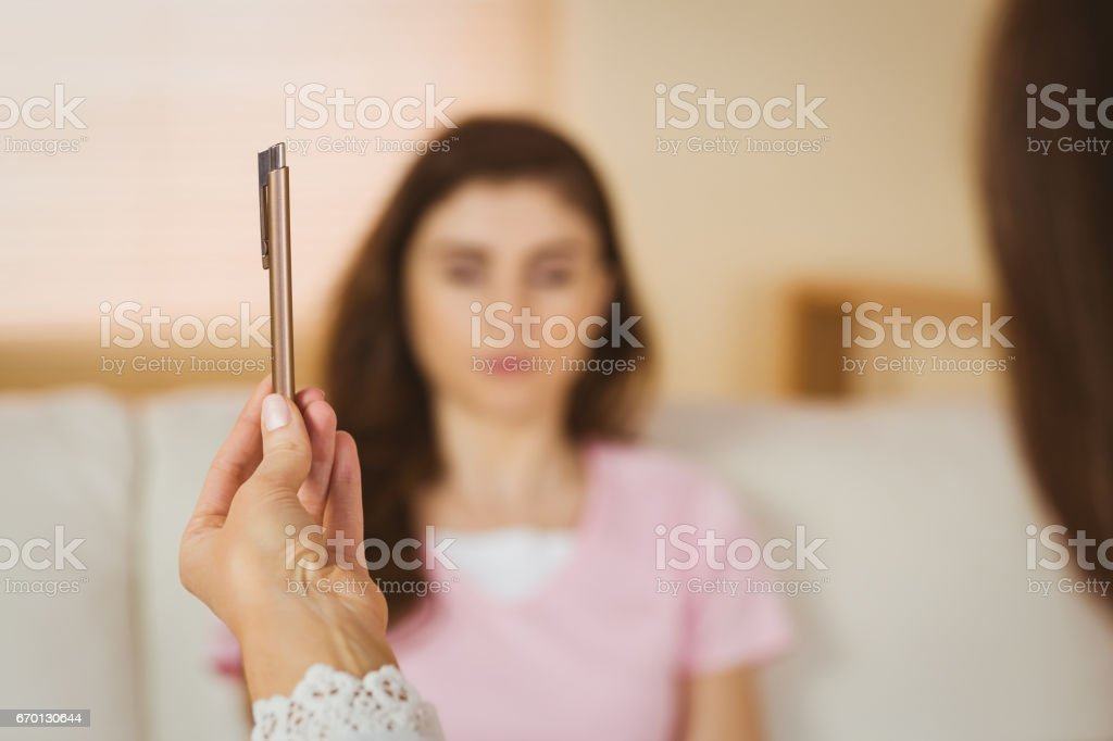 Hypnotherapist holding pen before her patient stock photo