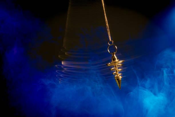 hypnotism pendulum swinging with motion blur - pendulum stock photos and pictures
